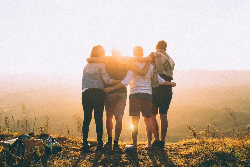 4 personer i ett team som håller om varandra i en solnedgång. Brist på samarbete och teamkänsla är en faktor som kan spela in om varumärket saknar en stabil grund.